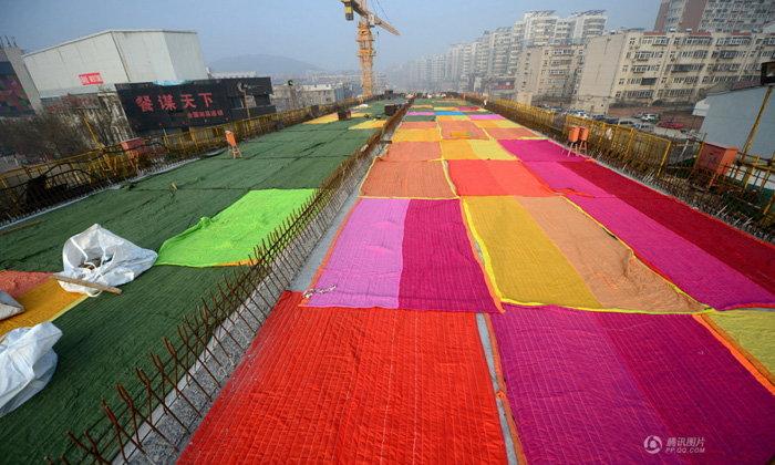 อุ่นเลย! คนงานก่อสร้างปูผ้านวมบนทางยกระดับกันปูนแห้งเร็วเกินไป
