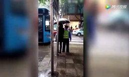ชาวเน็ตประทับใจ! หญิงชาวจีนยืนกางร่มให้ตำรวจทำงานกลางสายฝน