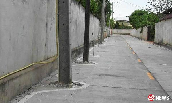 ชาวบ้านทึ่ง! เสาไฟฟ้าโผล่กลางถนน ตีเส้นโค้งเว้าสวยพิลึก